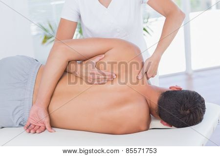 Physiotherapist doing back massage to her patient in medical office