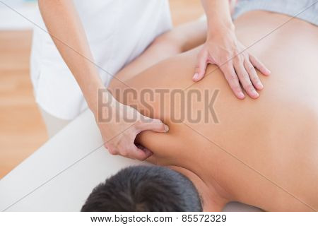 Physiotherapist doing shoulder massage to her patient in medical office
