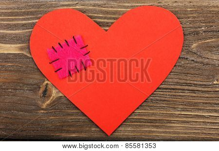 Patch on broken heart on wooden background