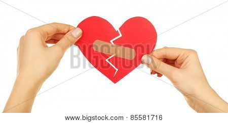 Female hands holding broken heart with plaster isolated on white