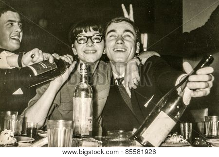 LODZ, POLAND, CIRCA 1960's: Vintage photo of young people having fun and drinking alcohol during a party