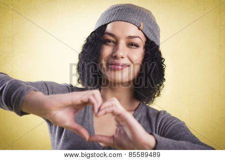 Love concept: Happy girl being cheerful and showing a heart sign with her fingers, isolated on yellow background with copyspace.