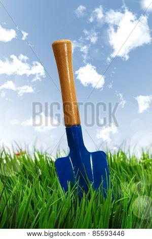 Shovel On Grass Over Sky