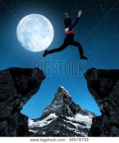 Girl jumping over the gap in night. In the background Matterhorn - Pennine alps, Switzerland
