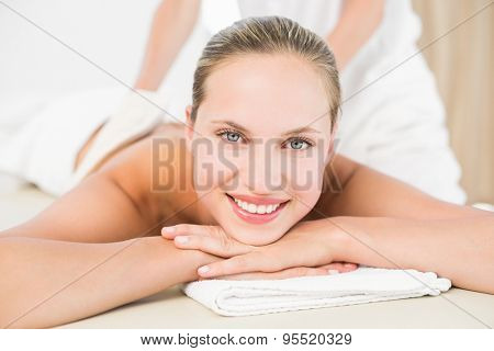 Peaceful blonde enjoying an exfoliating back massage in the health spa poster