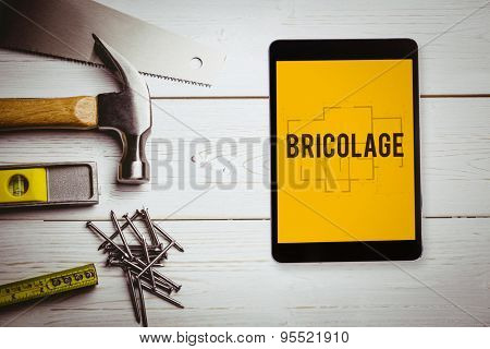 The word bricolage and tablet pc against blueprint