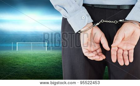 Businessman in formals with handcuffs against football pitch with lights and goalpost