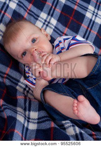 Cute baby boy nipping his feet