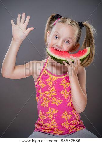 Little toothless girl eating watermelon.