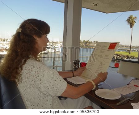 A Woman Reads The Menu At The Red Marlin