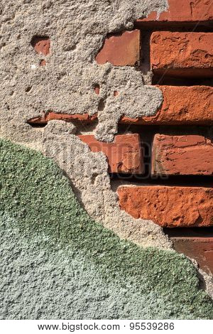 Crumbled gray green plaster on a brick wall