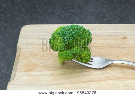 Green fresh vegetables. Broccoli with a fork on a cutting board
