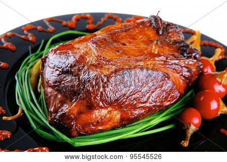roast red beef meat bbq bloc served on black plate  with green chives adn red hot pepper on black plate isolated over white background