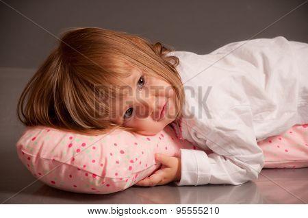 Sleepy little girl laying on a pillow