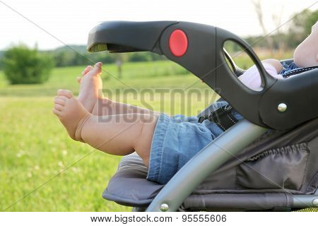 Newborn Infant Legs And Feet Hanging Out Of Stroller
