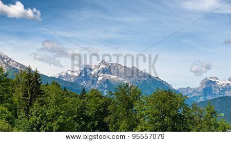 Close up of fir tree tops with rocky snow-capped mountain peaks in background, beneath blue sky with whispy white clouds