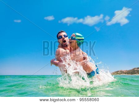 Father and his sun riseing from the sea water in a sunny summer day, splashes arround.
