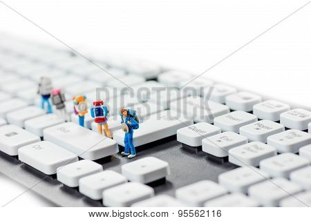 Miniature Backpackers On Top Of The Keyboard.