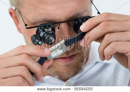 Man Looking Wrist Watch With Loupe
