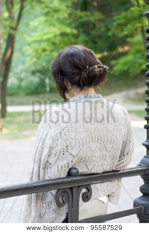 Young Beautiful Brunette In A Beige Jacket Is Tied Back, Leaning On The Fence