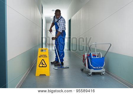 Male Janitor Mopping In Corridor