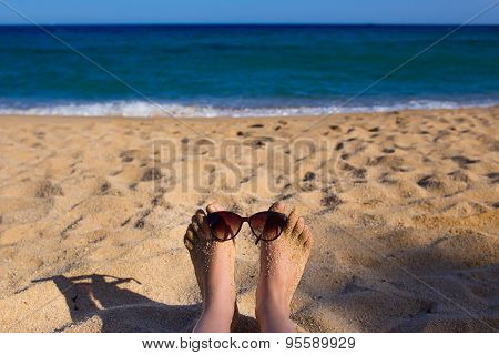 Luxury young woman legs and feet sunbathing on beach wearing sun glasses