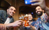 people, leisure, friendship, technology and bachelor party concept - happy male friends with smartphone taking selfie and drinking beer at bar or pub poster