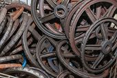 Rusted hand wheels of valves are stored in a warehouse,  Industrial area of old factory. poster