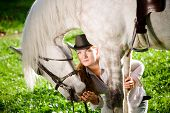Young Lady in hat hugging her horse poster