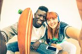 Hipster multiracial couple in love taking selfie on white background - Fun concept with alternative fashion and technology trends - Redhead girlfriend with afro american guy - Vintage filtered look poster