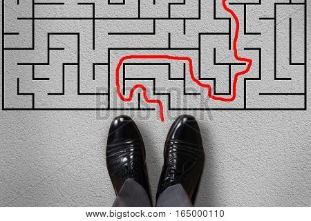 High Angle View Of Businessman Standing In Front Of Labyrinth