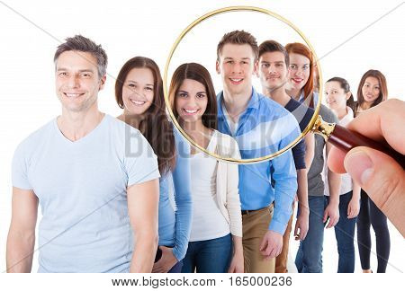 Person Hand Holding Magnifying Glass On Large Group Of Happy People Standing In Line On White Background