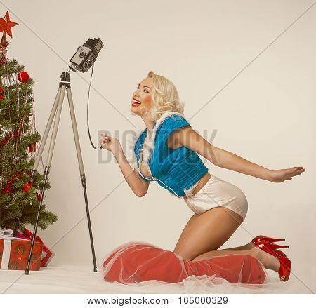 Beautiful Pin-up girl self photographing for the Christmas greetings