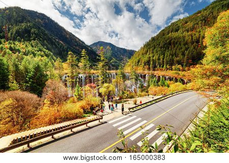 Top view of the Nuo Ri Lang Waterfall (Nuorilang) and road among wooded mountains and colorful fall forest in Jiuzhaigou nature reserve (Jiuzhai Valley National Park) China. Amazing autumn landscape.