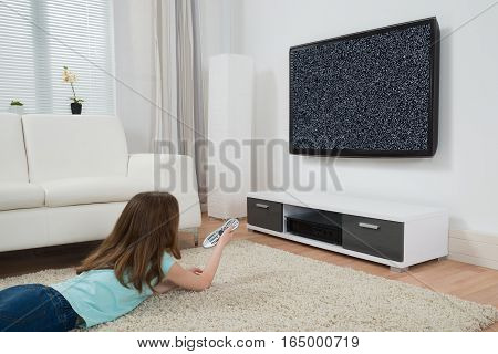 Girl With Remote Control Lying On Carpet In Front Of Television With No Signal