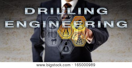 Manager in blue suit touching DRILLING ENGINEERING on an interactive computer screen. Oil and gas industry technology concept for technical support by engineers implementing safe drilling procedures.