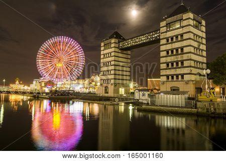 Ferris wheel and sluice gate under moon in Yokohama at night