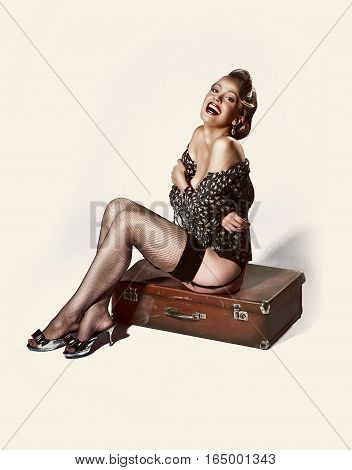 A beautiful young lady posing with a suitcase