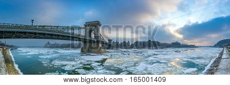 Budapest Hungary - The famous Szechenyi Chain Bridge on the icy River Danube with Parliament and Gellert Hill at background on a cold winter morning