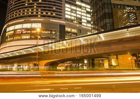 Overpass and light trail in front of building in Yokohama at night