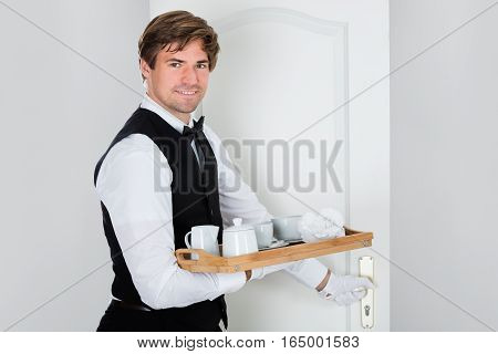 Happy Young Waiter Carrying Coffee Set On Wooden Tray And Opening Door