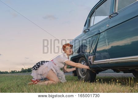 A woman kneels with a frustrated look next to the flat tire on her car