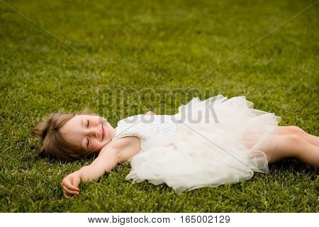 Little girl child in white dress lying on grass, eyes closed.