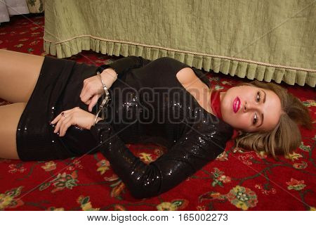 Strangled Beautiful Woman In A Black Dress Lies On The Floor. Simulation Of The Crime Scene.