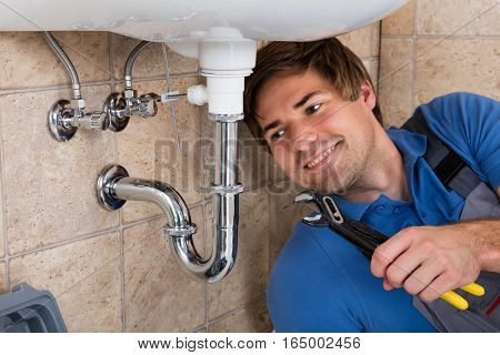 Happy Young Male Plumber Repairing Sink In Bathroom With Wrench