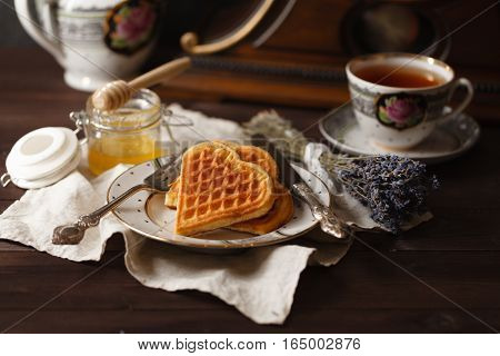 Viennese wafers with tea and honey on table