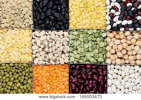 Pulses food background assortment - legume kidney beans peas lentils in square cells closeup top view. Healthy protein food.