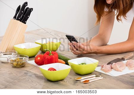 Close-up Of Woman Using Mobile Phone At Countertop In Kitchen