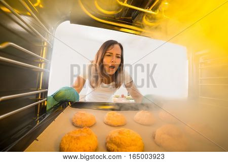Shocked Young Woman Looking At Burnt Cookies In Oven