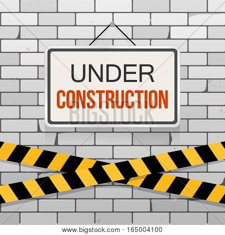 Simple white sign with text 'Under Construction' hanging on a gray brick wall with warning tapes. Grunge brickwork background. Building engineering concept. Creative template for web design